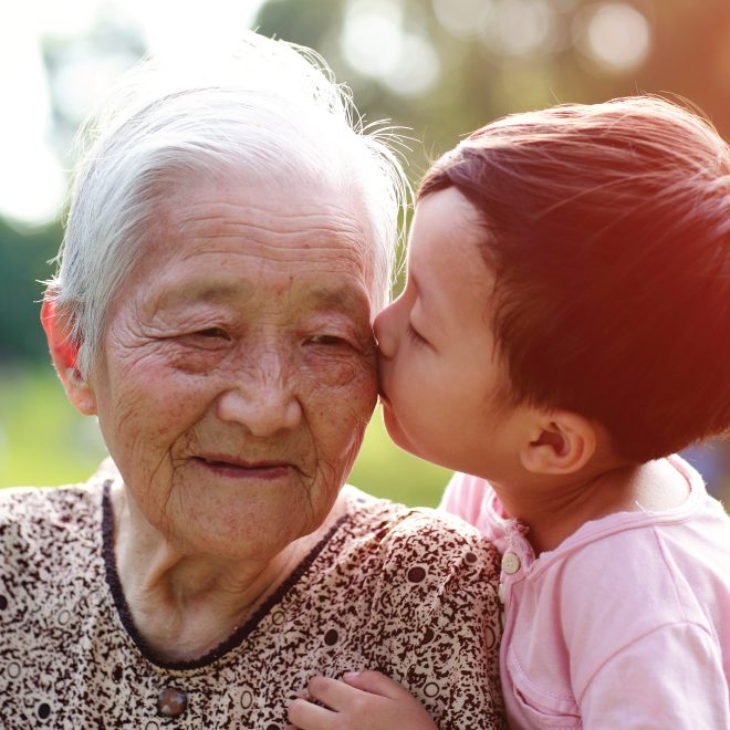 Senior Asian woman receiving a kiss on the cheek from her great grandchild