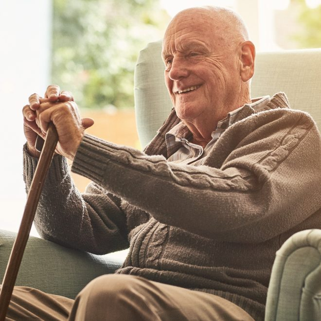 Senior man relaxing in a chair, smiling and holding his cane