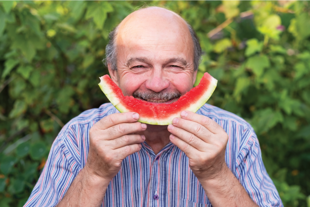 Man holding eaten watermelon rind as a smile face